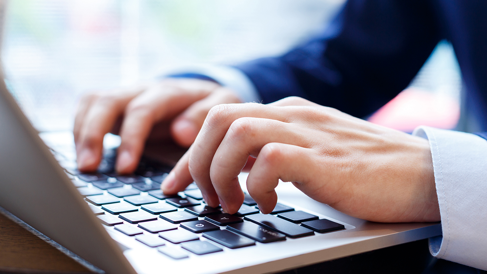Close up of hands typing at a laptop keyboard.